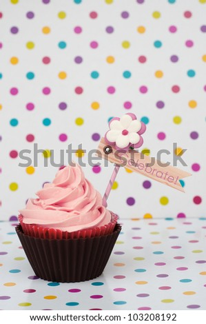 Cupcake with pink whipped cream and flag