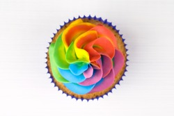 Cupcake with rainbow colorful cream in blue cup on white wooden table. Top view.