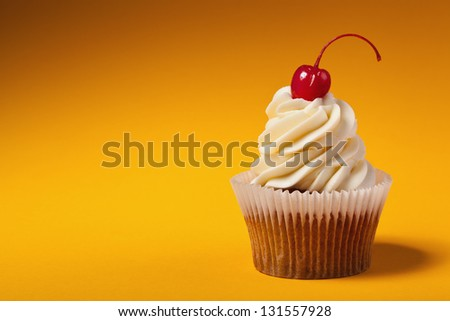 cupcake with red cherry isolated on orange background with copyspace