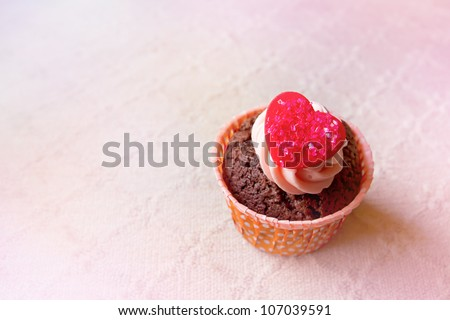 cupcake with valentine heart icing closeup in pastel tone