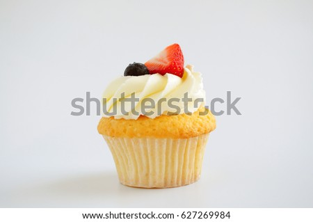 Cupcake with whipped cream, fresh strawberry, blueberry on white background. Isolated. Picture for a menu or a confectionery catalog.