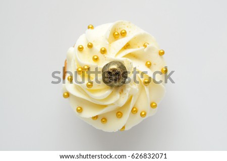 Cupcake with white cream, blueberry and gold confectionery sprinkling. Top view. Picture for a menu or a confectionery catalog.