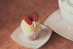 cupcake with white cream decorated with fresh strawberries on the table, accompanied by a white teapot and cup.