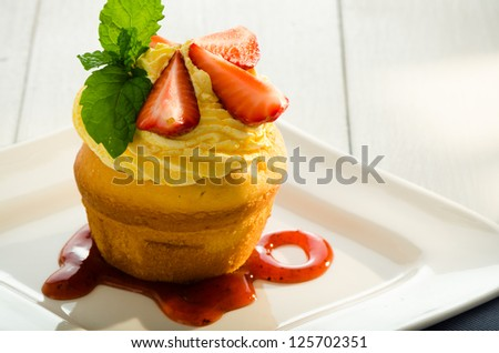 cupcake with yellow cream fresh mint leaves and strawberry as decoration strawberry sauce on the plate