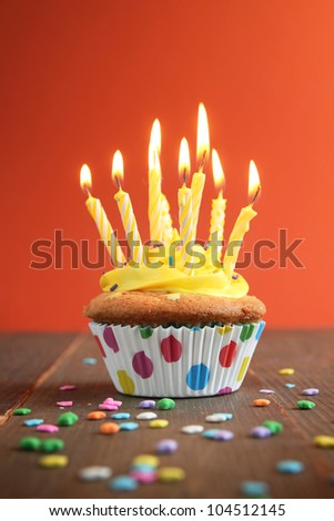 Cupcake with yellow icing full of yellow candles on orange background