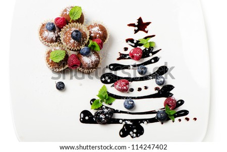 Cupcakes and sweet christmas tree with berries and mint isolated on white