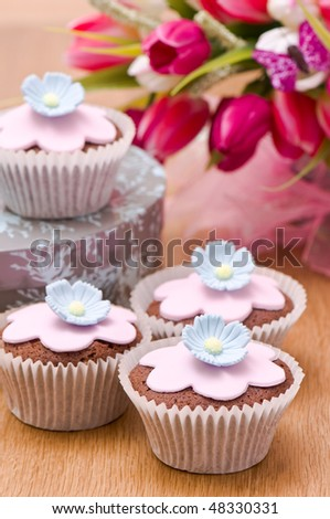 Cupcakes decorated with flowers for springtime with tulips in background