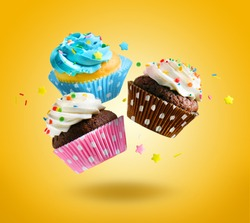 Cupcakes flying over yellow background. Colorful festive cupcakes for party, birthday.