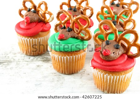 Cupcakes of red and green decorated to look like Rudolph.  Shot with selective focus and a shallow depth of field.