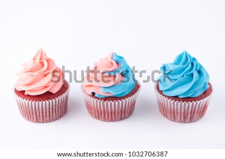 Cupcakes red velvet with blue and pink whipped cream on white background. Picture for a menu or a confectionery catalog.