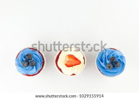 Cupcakes red velvet with blue and white whipped cream decorated with blueberry, strawberry on white background. Picture for a menu or a confectionery catalog. Top view.