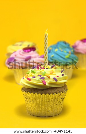 cupcakes shot on a yellow background with one candle