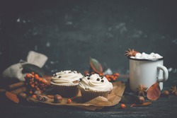 Cupcakes with autumn decorations on the rustic wooden background. Shallow depth of field. Toned image.