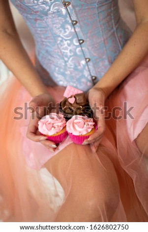 Cupcakes with beautifully decorated cream are held in hands by a girl in a beautiful dress and light manicure on a background of pink and blue clothes