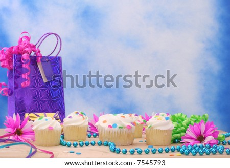 Cupcakes with Birthday Gifts and Flowers on Blue Sky Background