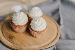 Cupcakes with buttercream stand on a wooden stand.