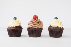 Cupcakes with whipped chocolate and vanila cream, decorated fresh strawberry, blueberry, gold confectionery sprinkling on white wooden table. Picture for a menu or a confectionery catalog.