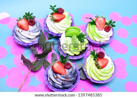 cupcakes with whipped cream decorated chocolate bar, strawberry ,macaroons on blue background. Picture for a menu or a confectionery catalog. with space for text. decorated with pink confetti.