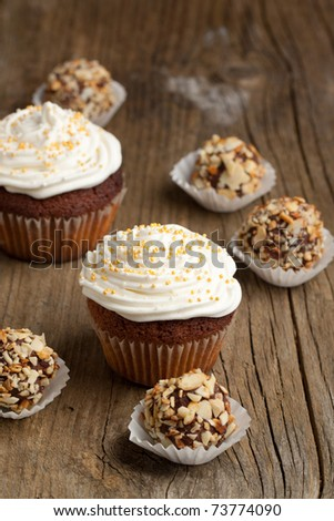 Cupcakes with whipped cream with chocolate truffles on old wooden table - stock photo