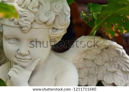 Cupid little Angel Stucco The god of love is hidden in a tree.Stucco art ornamental garden