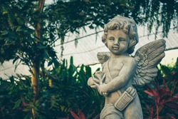 Cupid sculpture in the garden, cute cupid statue decoration in the outdoor wedding celebration. new valentine's day cupids play a bird in garden