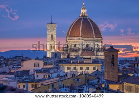 Cupola and bell tower of cathedral Santa Maria del Fiore in Florence, Itlay. Church iluminated by lights in the dusk. Beautiful pink and blue sky.