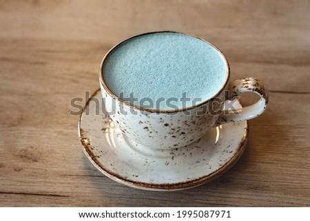Cupp of blue matcha tea latte on oat milk in ceramic mug on wooden table Stok fotoğraf ©