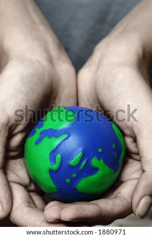 Cupped hands holding planet Earth