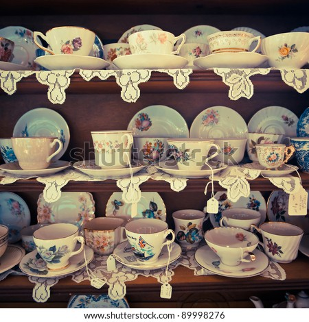 Cups and saucers on display in an antique shop.