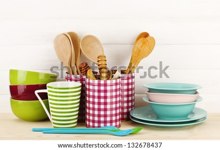 Cups, bowls nd other utensils in metal containers isolated on light background