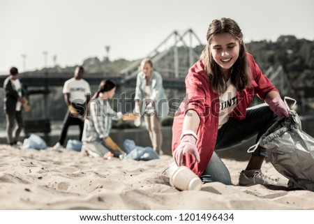 Cups in bag. Young dark-haired student wearing red anorak putting cups into garbage bag while volunteering on the beach