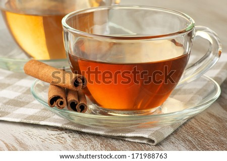 Cups of black and green tea with cinnamon on rustic table.