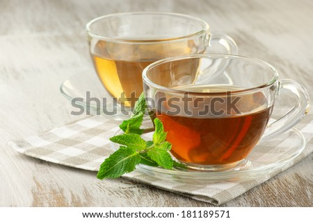 Cups of black and green tea with mint on rustic table.