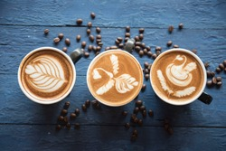 cups of cappuccino with latte art on blue wooden background,top view,flat lay