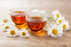 cups of chamomile tea with fresh chamomile flowers on a wooden table