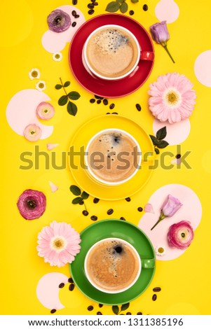 Cups of Coffee and colorful paper circles on yellow paper background, flat lay