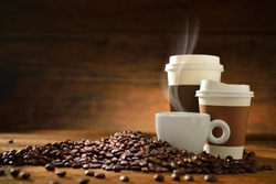 Cups of coffee with smoke and coffee beans on old wooden background