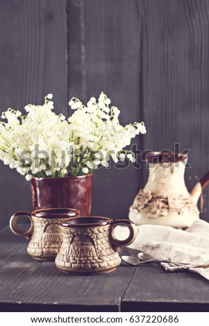 Cups of espresso and lily of the valley on a background of old wooden boards. Rustic style. #637220686