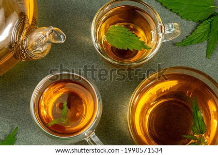Cups of herbal tea, transparent teapot and nettle leaves on green background. Calming drink concept. Top view Flat lay. Foto stock ©