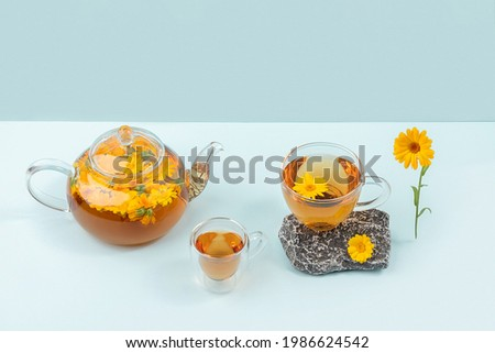 Cups of herbal tea, transparent teapot with calendula flowers and stones on blue background. Calming drink concept. Foto stock ©
