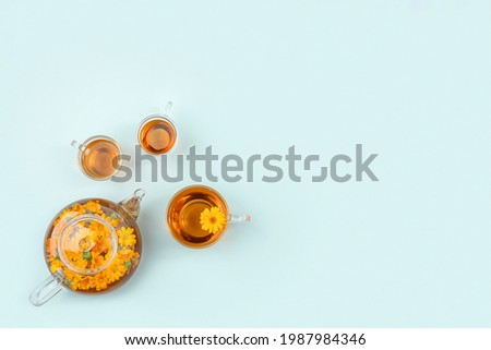 Cups of herbal tea, transparent teapot with calendula flowers on blue background. Calming drink concept. Copy space Flat lay Top view. Foto stock ©