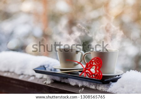 Cups of tea or coffee with steam,heart shape on blurred background. Valentine's day celebration or love concept. Copy space.love and coffee, hot drinks outdoor, on Balcony,terrace, patio.Romantic