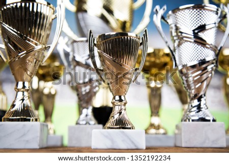 Cups of winners award on white podium, sport background #1352192234