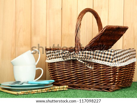 cups, plates and basket on grass on wooden background