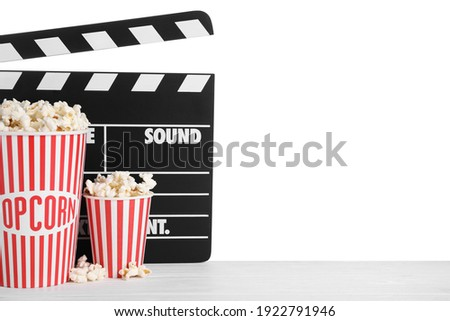 Cups with delicious popcorn and clapperboard on wooden table against white background