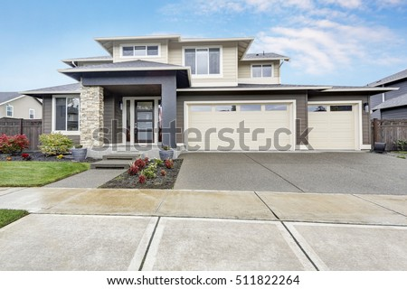 Curb appeal of brand-new home in brown and beige colors with two garages and concrete driveway. Northwest, USA #511822264