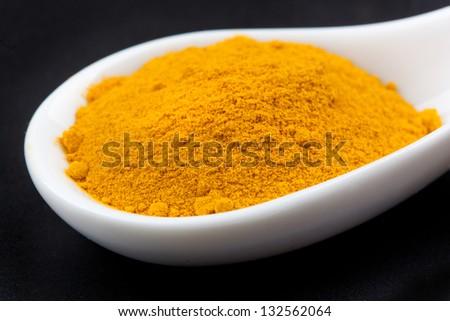 curcuma powder in white spoon on black table