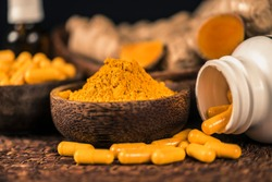 Curcumin supplement capsules, turmeric powder in glass bowl and curcuma root in background. Herbal medicine Curcuma against inflammation
