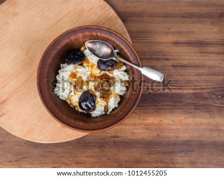 Curd in an earthenware bowl with the raisins, and dried apricots drizzled with honey on background of the table and cutting board. Healthy meals Illustration for blog articles or advertising.
