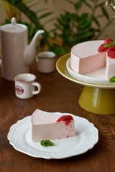 Curd mousse with strawberries sauce. Wood background. Orchid. Side View. Strawberries, mint,  coffee and home flowers. Cheescake. Piece of cake.